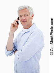Portrait of a mature man making a phone call while looking at the camera against a white background