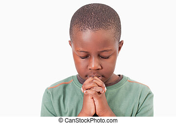 Young boy praying against a white background