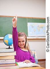 Portrait of young schoolgirl raising her hand in a classroom