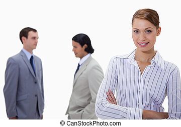 Businesswoman with arms folded and talking colleagues behind her against a white background