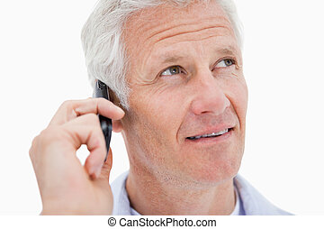 Mature man making a phone call while looking up
