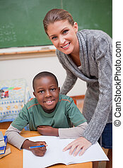 Portrait of a teacher explaining something to a smiling schoolboy