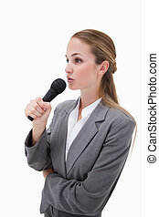 Side view of woman with microphone against a white...