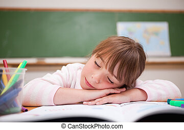 Schoolgirl sleeping on a desk in a classroom