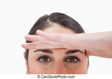 Close up of a woman with her hand on her forehead against a...