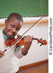 Portrait of a boy playing the violin in a classroom