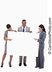 Businesspeople pointing and looking at blank sign against a...