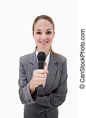 Smiling woman holding microphone against a white background