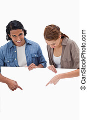 Smiling couple pointing down on blank wall