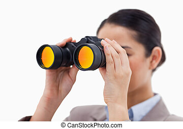 Brunette businesswoman looking through binoculars