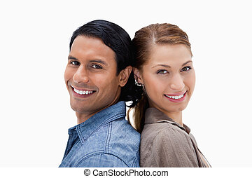 Side view of smiling couple standing back to back