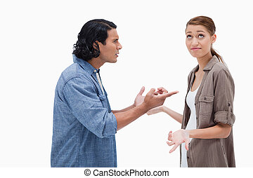 Side view of tensed talking couple against a white...
