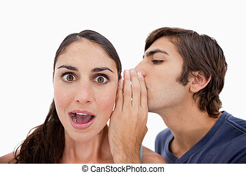 Man whispering something shocking to his fiance against a...