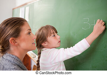 Teacher and a pupil making an addition on a blackboard