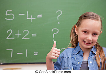 Schoolgirl with the thumb up in front of a blackboard