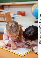 Portrait of focused schoolgirls reading a fairy tale in a...
