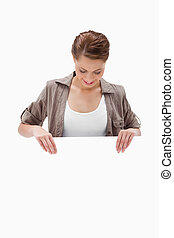 Woman looking down at blank signboard
