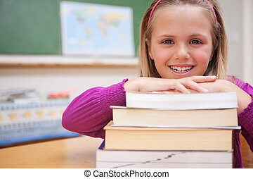 Schoolgirl posing with a stack of books in a classroom