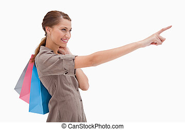Side view of pointing woman with shopping bags