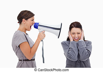 Businesswoman yelling at colleague with megaphone against a...