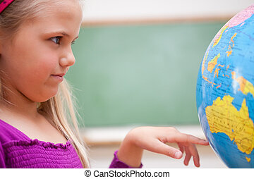 Close up of a schoolgirl looking at a globe