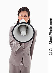 Angry businesswoman yelling through megaphone against a...