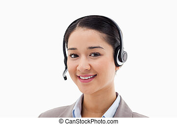 Smiling operator posing with a headset against a white...