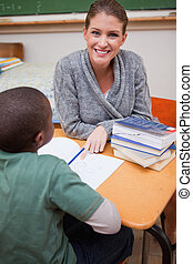 Portrait of a happy teacher explaining something to a pupil