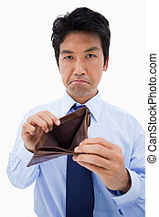 Portrait of a businessman showing his empty wallet against a...