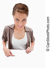 Smiling woman pointing down at blank signboard