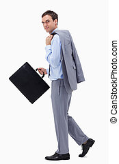 Side view of walking businessman with suitcase against a...