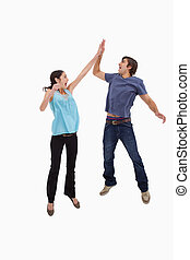 Portrait of a couple jumping together against a white...