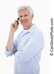 Portrait of a happy man making a phone call while looking at the camera against a white background
