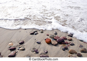 Sea waves beat stones lying in sand on coast line - Sea...