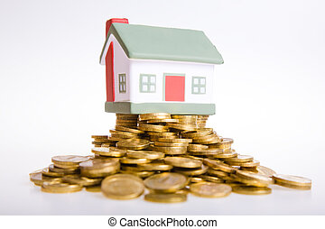 Toy small house standing on a heap of coins.