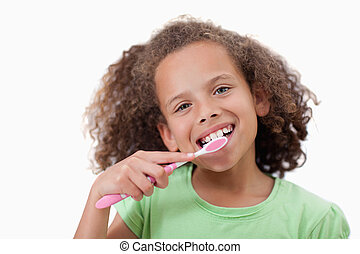 Cute girl brushing her teeth against a white background