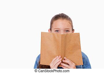 Girl hiding her face behind a book