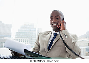 Smiling businessman on the phone while reading a document in...