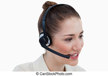 Close up of an operator talking through a headset against a...