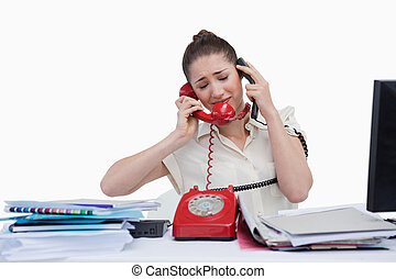 Overburden businesswoman answering the phones against a...