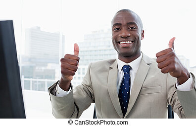 Businessman working with a computer with the thumbs up in...