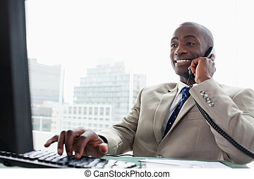 Businessman on the phone while using a computer