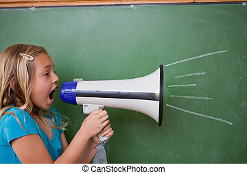 Young schoolgirl screaming through a megaphone in front of...