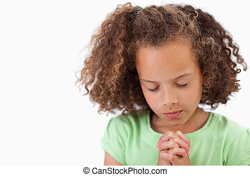 Cute girl praying against a white background
