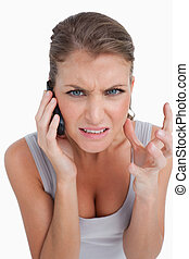 Portrait of an angry woman making a phone call against a...