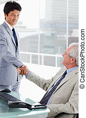Portrait of a smiling employee shaking the hand of his manager