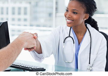 Smiling female doctor shaking a hand in her office