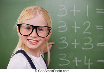 Smiling smart schoolgirl pointing at something on a...
