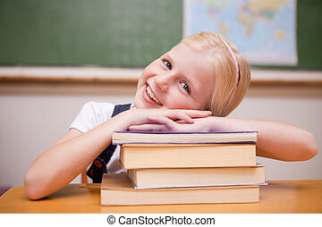 Smiling girl leaning on books