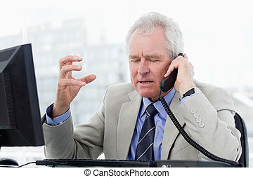 Irritated senior manager on the phone in his office